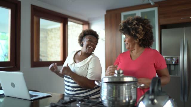 vídeos de stock, filmes e b-roll de amigas dançando e cozinhando juntas em casa - adulto maduro