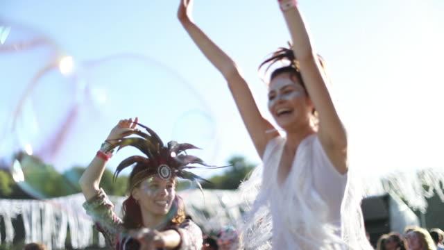 Female friends dancing at summer festival