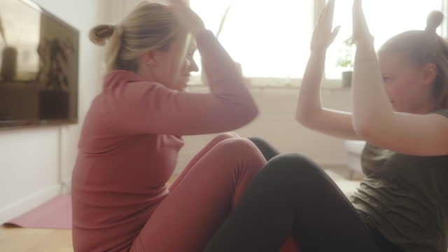 female friends doing sit-ups together at home - sit ups stock videos & royalty-free footage
