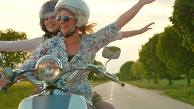 vídeos y material grabado en eventos de stock de slow motion las amigas femeninas disfrutan montando ciclomotor retro - amistad femenina