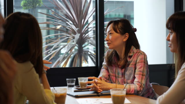 女性の友人がカフェで会話を楽しむ - 親睦会点の映像素材/bロール