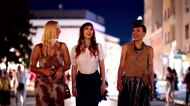 vídeos de stock, filmes e b-roll de a pé femininos amigos, desfrutando de uma noite na cidade - três pessoas