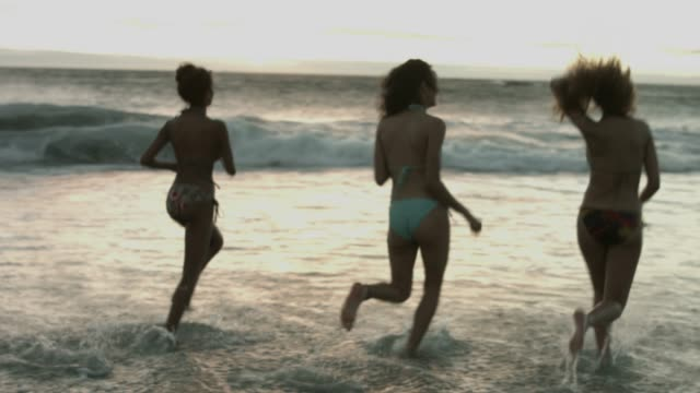 female friends enjoying at beach during sunset - ビキニ点の映像素材/bロール