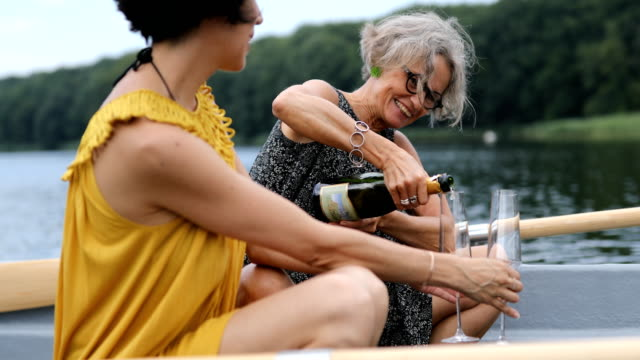 Female friends enjoying champagne in boat