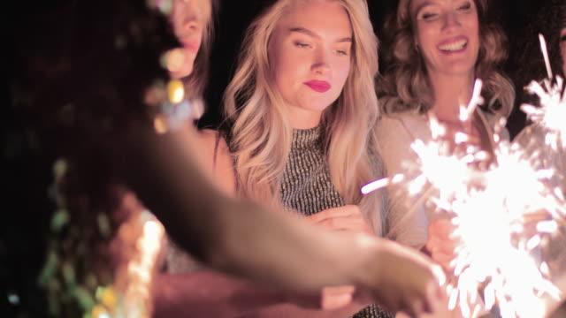 vídeos de stock, filmes e b-roll de female friends having fun with sparklers on an urban rooftop - despedida de solteira