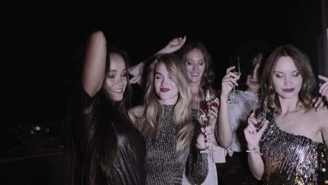 vídeos de stock, filmes e b-roll de female friends having hen party on urban rooftop and drinking champagne - despedida de solteira