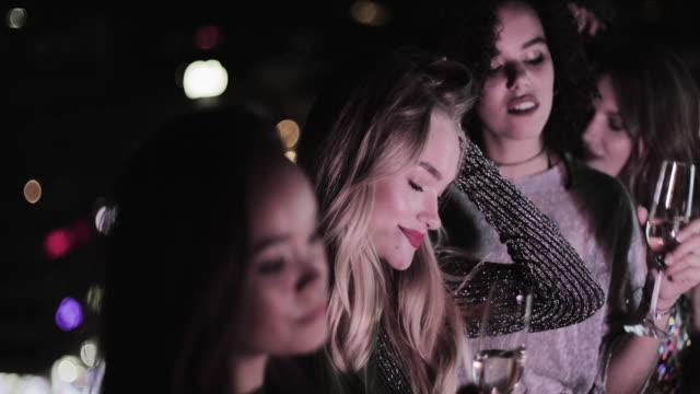 vídeos de stock, filmes e b-roll de female friends having hen party on urban rooftop - despedida de solteira