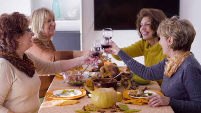 female  friends  having thanksgiving lunch and cheers with red wine - dinner party stock videos & royalty-free footage