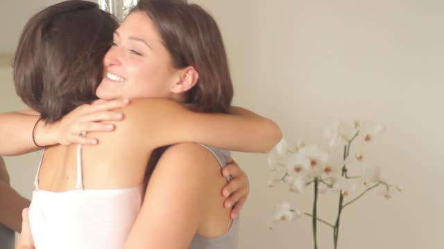 stockvideo's en b-roll-footage met female friends hugging and kissing - kussen beddengoed