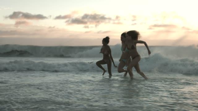 female friends in bikinis enjoying at beach - ビキニ点の映像素材/bロール