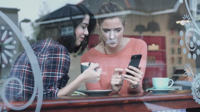 Female friends in coffee shop looking at smart phone