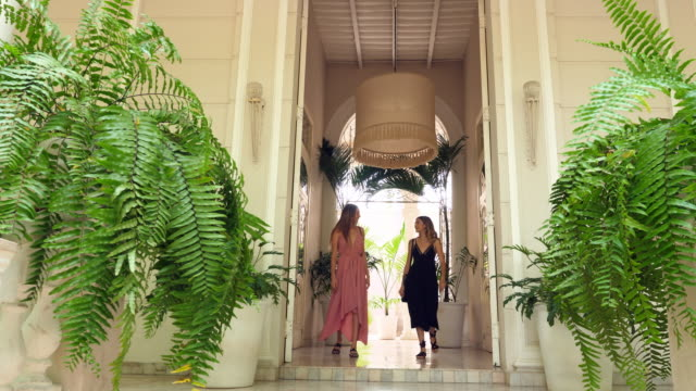 ms female friends in discussion while walking through entryway in villa - dress stock videos & royalty-free footage