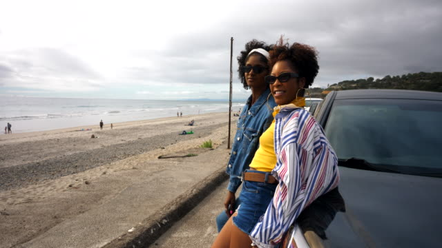 ms female friends leaning on hood of car while parked at beach - bonnet stock videos & royalty-free footage