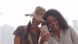 Female Friends Look At Photos On Phone By Manhattan Skyline