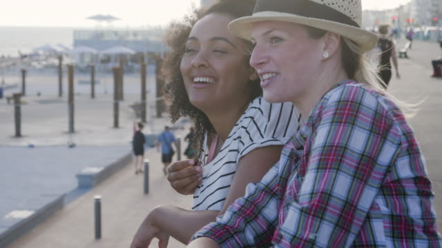 female friends look out over beach, standing on promenade. - city break stock videos & royalty-free footage