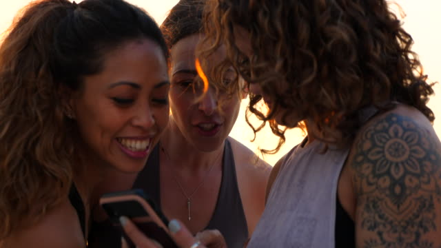 ms female friends looking at smart phone after sunset rooftop yoga class - three people stock videos & royalty-free footage