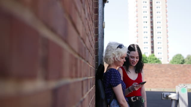 Female friends looking at smartphone and leaning against brick wall