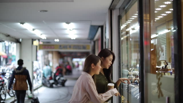 female friends looking at window store in shopping mall - window display stock videos and b-roll footage