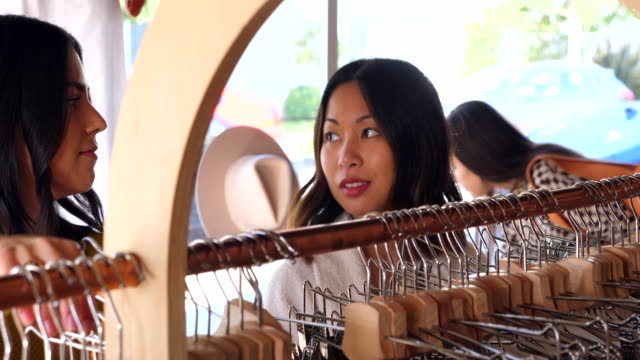 ms female friends looking though clothing rack while shopping in boutique - clothes shop stock videos & royalty-free footage