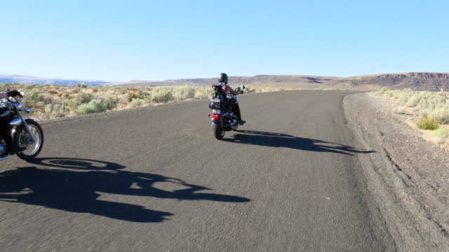 ws female friends on motorcycle road trip through desert on summer evening rear view - gender bender video stock e b–roll