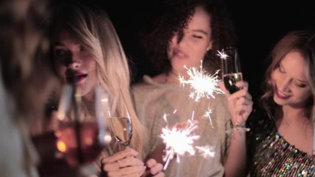 vídeos de stock, filmes e b-roll de female friends party on rooftop at night with sparklers - despedida de solteira