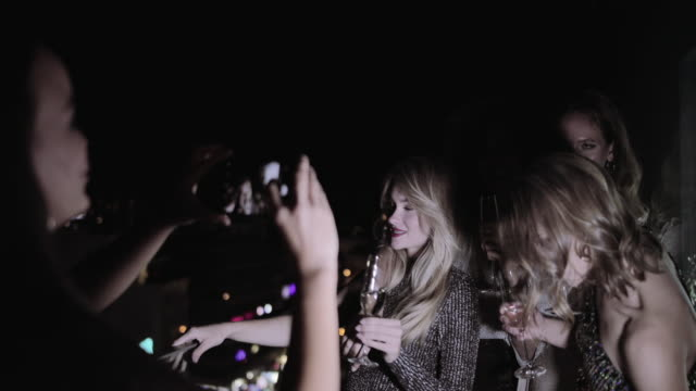 female friends partying on urban rooftop and taking picture with smart phone - cocktail dress stock videos & royalty-free footage