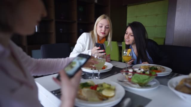 female friends photographing food on lunch break - foodie stock videos & royalty-free footage