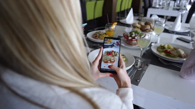 female friends photographing food on lunch break - business lunch stock videos & royalty-free footage