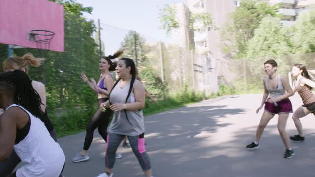 vidéos et rushes de amis féminins jouant au basket-ball sur le terrain de sports - streetball