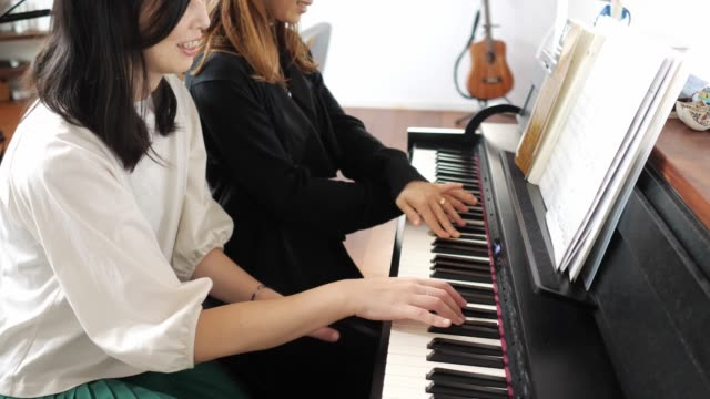 vídeos de stock e filmes b-roll de female friends playing the piano together - pianista