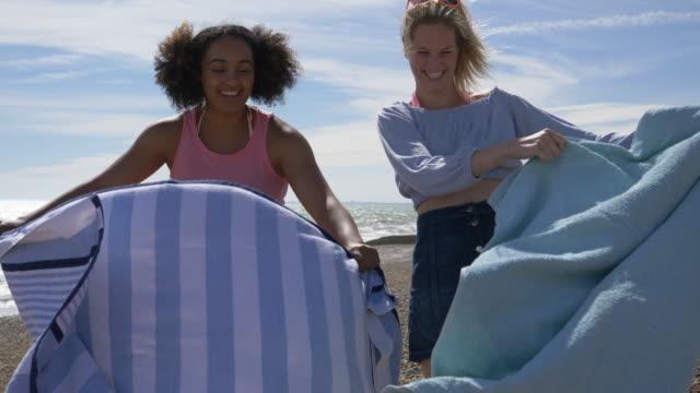vídeos de stock, filmes e b-roll de female friends putting down beach towels on windy beach. - toalha de praia