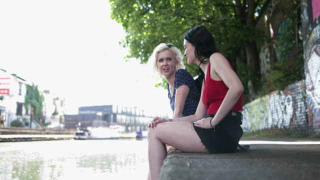 Female friends relaxing by canal in urban city