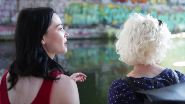 female friends relaxing by canal in urban city - canal stock videos & royalty-free footage