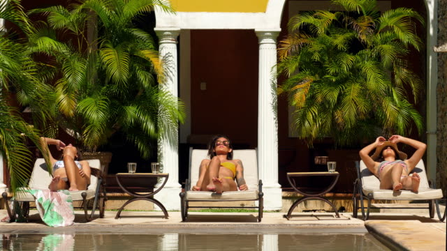ms female friends relaxing together in lounge chairs by pool in courtyard of boutique hotel - sonnenbrille stock-videos und b-roll-filmmaterial