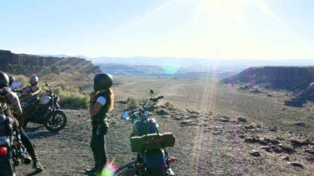 ws pan female friends resting at canyon overlook at sunset during motorcycle road trip - ヘルメット点の映像素材/bロール