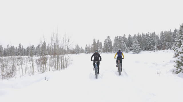 ts ms female friends riding fat tire bikes on snow covered forest road on winter afternoon - mountain biking stock videos & royalty-free footage