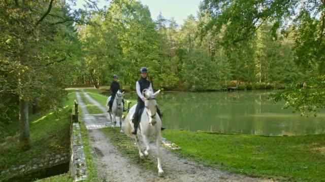 vidéos et rushes de cs amis femelles équitation chevaux blancs à travers un pont de lac - eau dormante