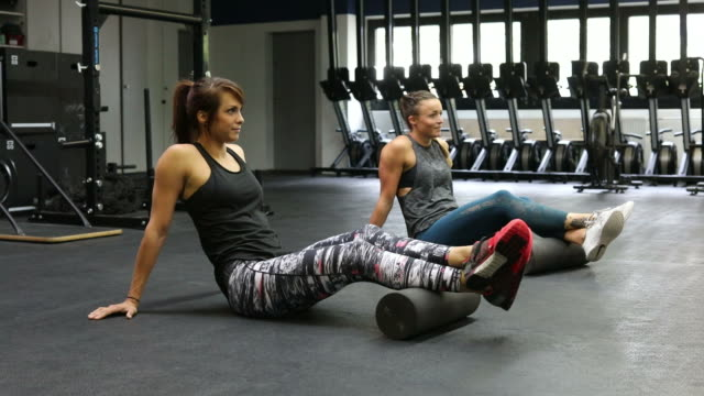 female friends rolling legs on foam rollers in health club - pampering self stock videos and b-roll footage