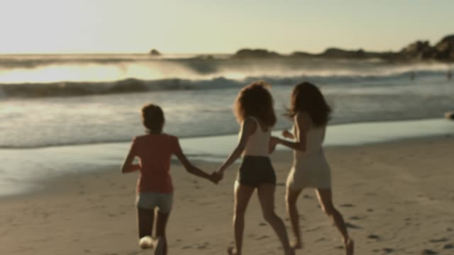 female friends running towards sea shore - 18 19 years stock videos & royalty-free footage