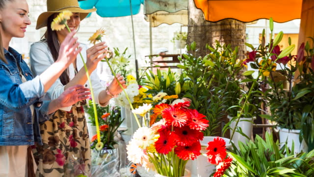 MS female friends selecting flowers in market