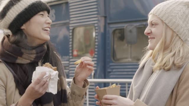 Female friends sharing streetfood, laughing and chatting at outdoor food market.
