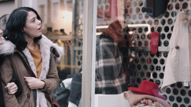Female friends shopping and looking at shop window