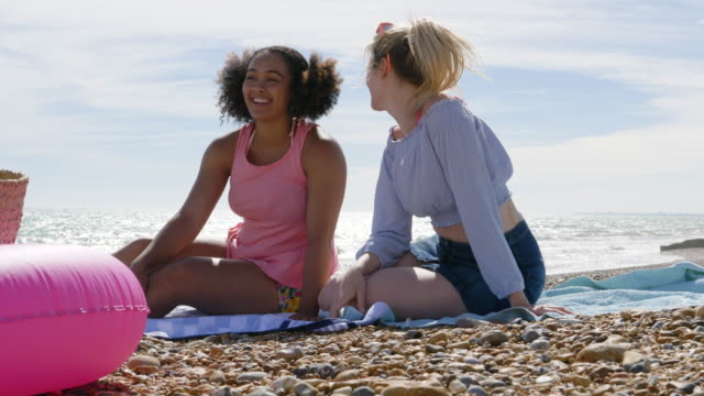 female friends sitting on beach talking and laughing. - brighton england stock videos & royalty-free footage