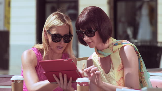 Female friends sitting outside while chatting and looking at tablet