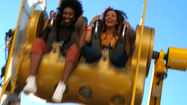 MS Female friends spinning upside down on ride in amusement park