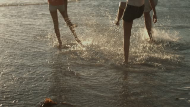 female friends splashing water at beach - barefoot点の映像素材/bロール