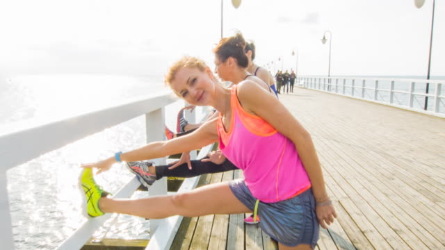 Female friends stretching on a jetty