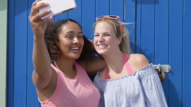 female friends take selfies on smart phone near beach hut. - 英格蘭 個影片檔及 b 捲影像