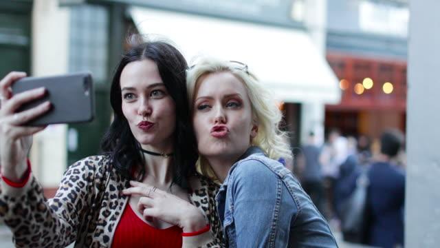 female friends taking a selfie on a night out - 口を尖らせる点の映像素材/bロール