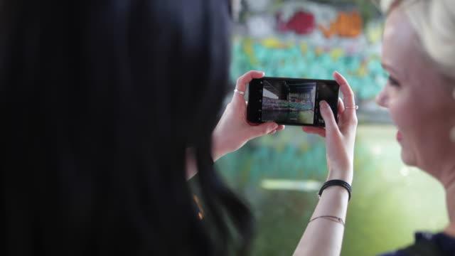 vídeos de stock e filmes b-roll de pov female friends taking photo of graffiti street art - grafite produto artístico